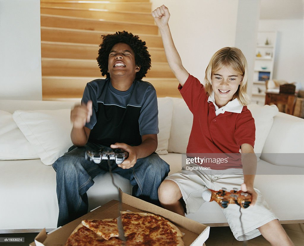 Two Boys Sitting on a Sofa Playing a Computer Game, with One Boy Raising His Fist in Success : Stock Photo