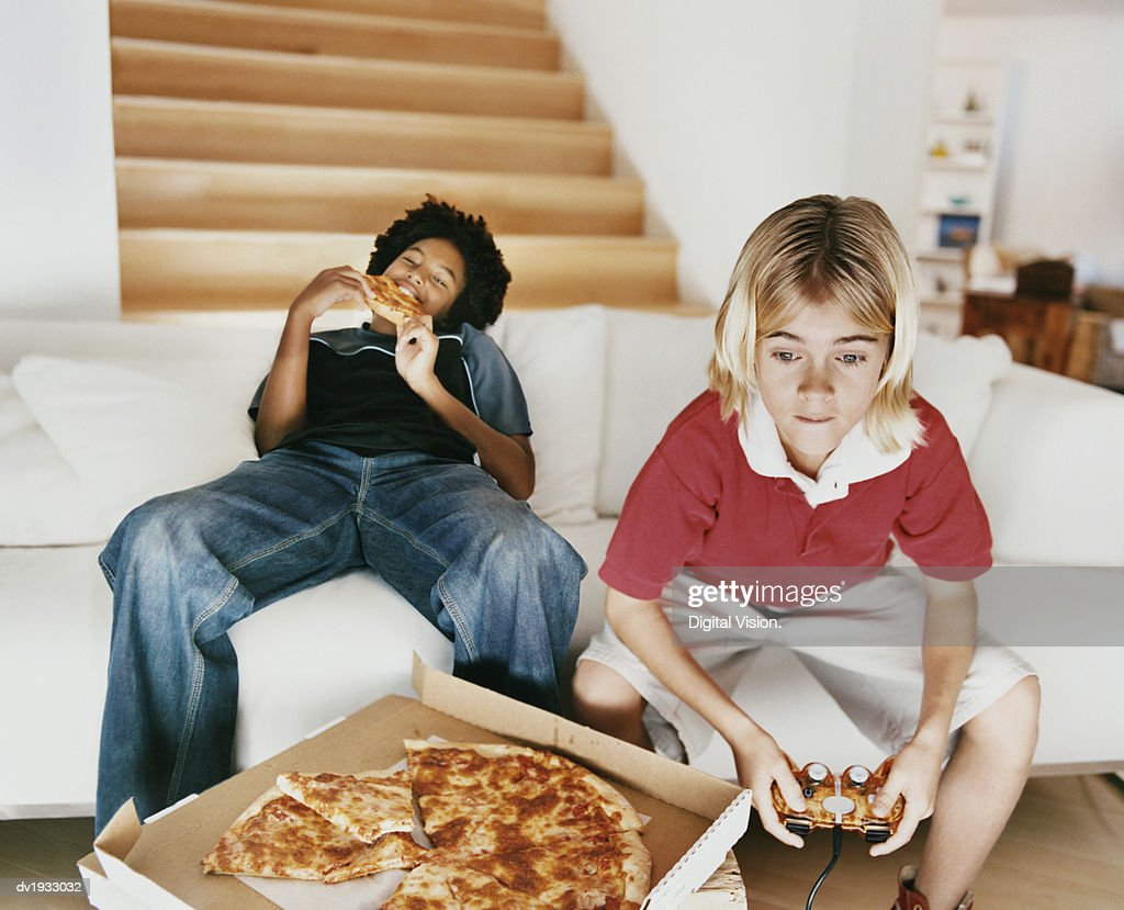 Two Boys Sitting on a Sofa, with One Boy Eating a Slice of Pizza and the Other Playing a Computer Game : Stock Photo