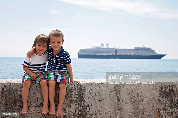 Two boys, sitting on a wall, ship in the sea