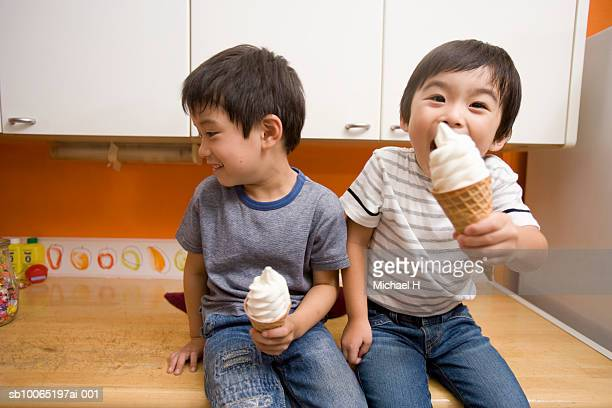 Two boys (4-5) sitting on kitchen counter, eating ice-cream