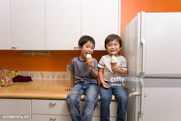 Two boys (4-5) sitting on kitchen counter, eating ice-cream, portrait