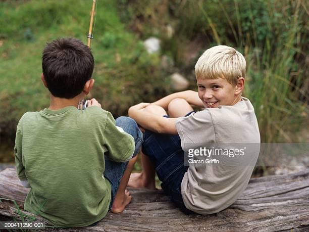 Two boys (9-11) sitting on rock fishing, smiling, portrait, rear view