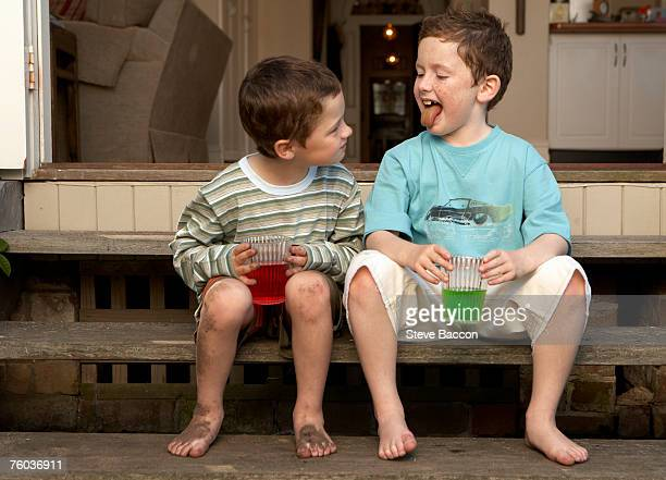 Two boys (6-7, 8-9)  sitting on steps outdoors, drinking colourful beverages