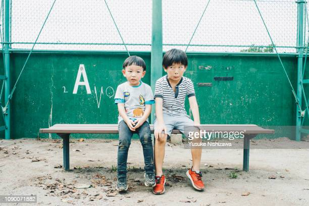 two boys sitting on the bench - yusuke nishizawa stock pictures, royalty-free photos & images