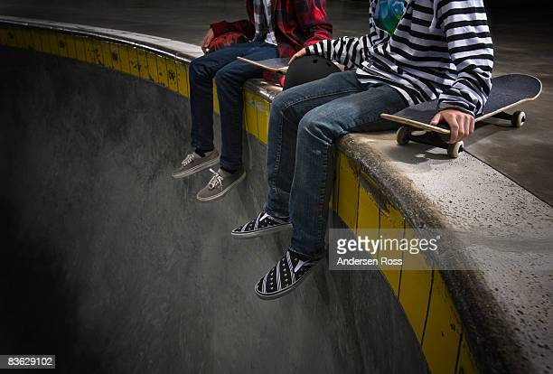 Two boys sitting on the edge of skate park