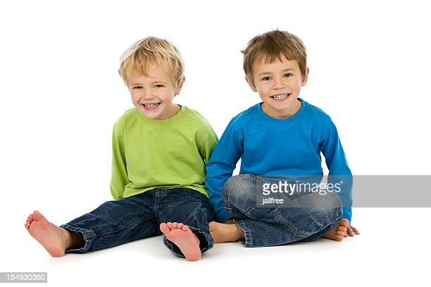 Two boys sitting on white background smiling