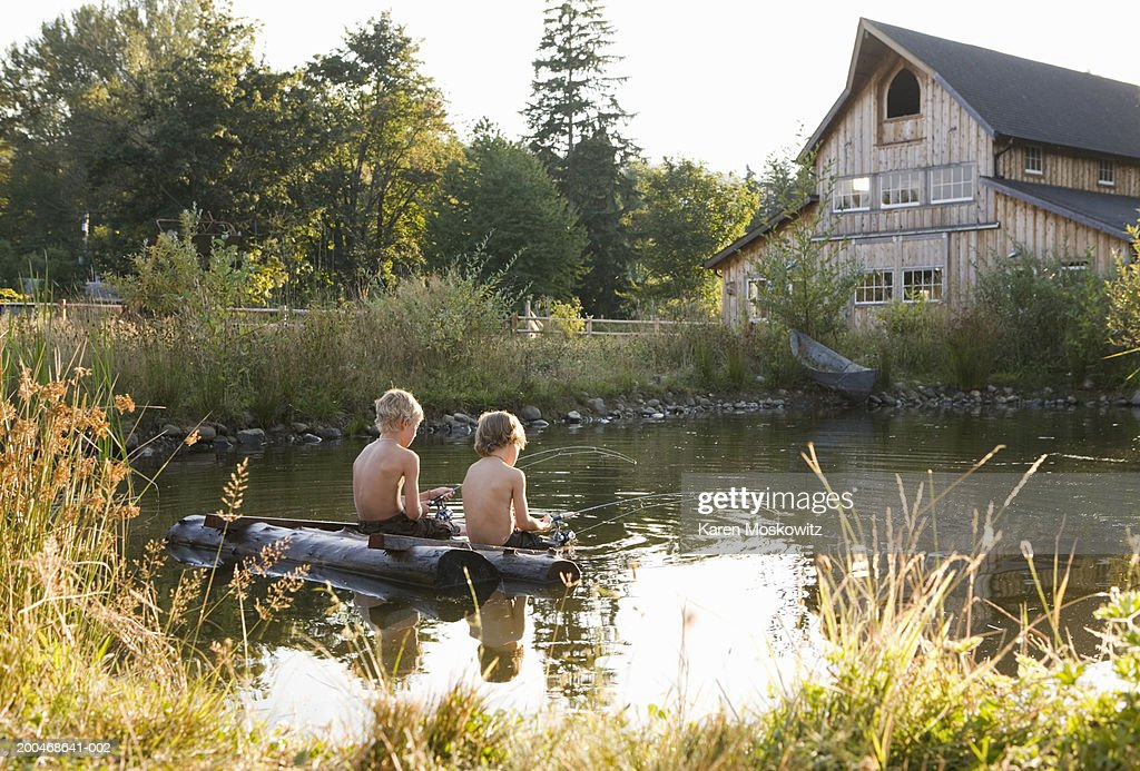 Two boys (5-8) sitting on wooden raft, fishing in pond, rear view : Stock Photo