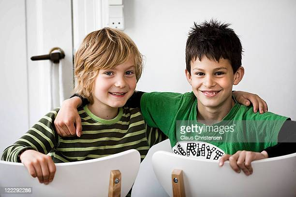two boys sitting with hands over shoulders