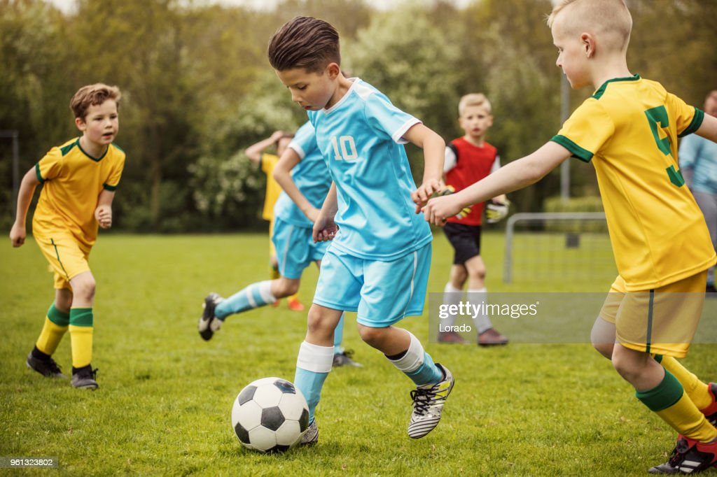 Two boys soccer teams competing for the ball during a football match : Stock Photo