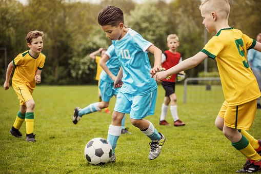 Two boys soccer teams competing for the ball during a football match 961323802