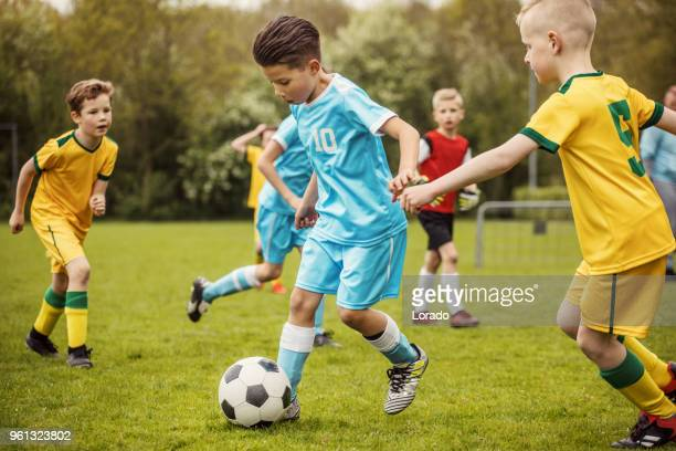 two boys soccer teams competing for the ball during a football match - sports team event stock photos and pictures