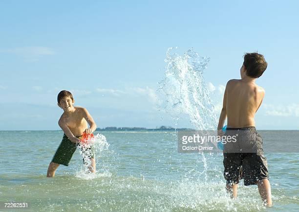 Two boys splashing in water at beach