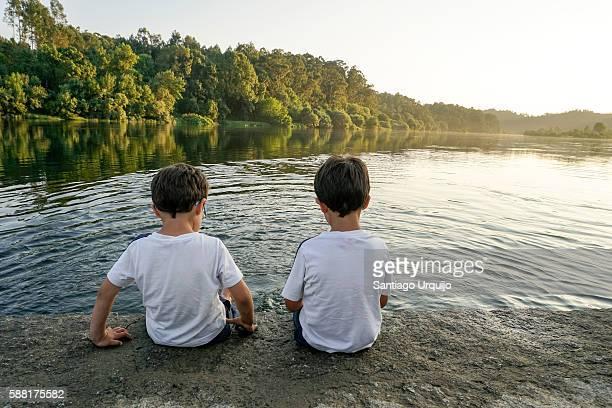 Two boys splashing on the Minho river