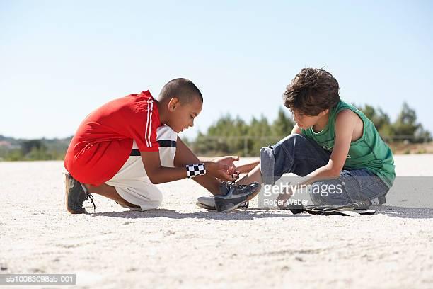 Two boys (9-11) squatting on sand, tying shoelaces