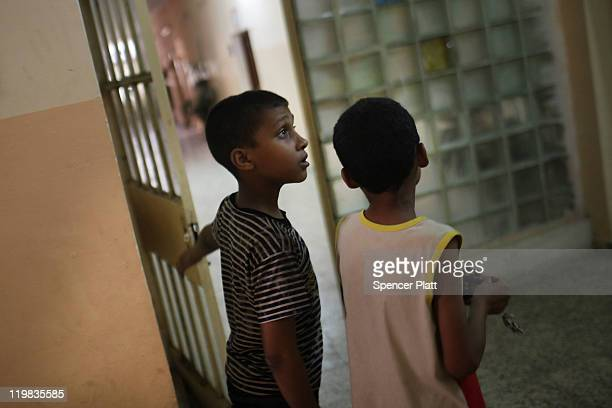Two boys stand in a hallway of the Al-Baraum orphanage on July 25, 2011 in Baghdad, Iraq. The state owned orphanage has about 50 children currently...