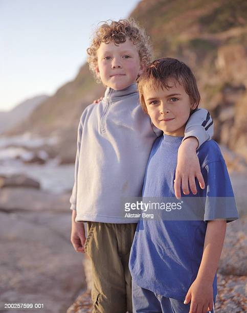 Two boys (6-8) standing arm in arm outdoors, portrait
