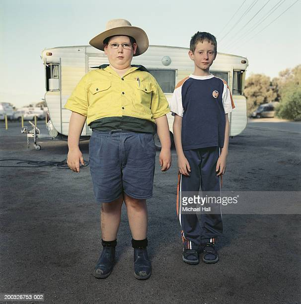 two boys (6-8) standing by caravan, portrait - side by side stock pictures, royalty-free photos & images