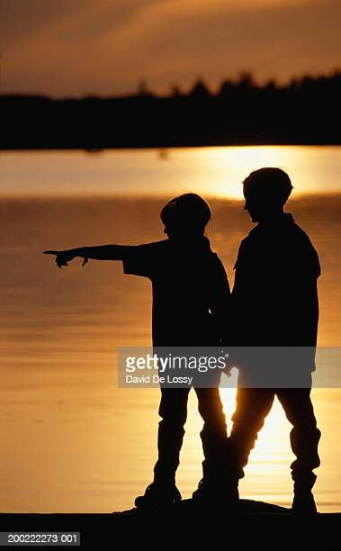 two boys (10-11) standing by lake at sunset, side view - 10 11 jahre stock-fotos und bilder