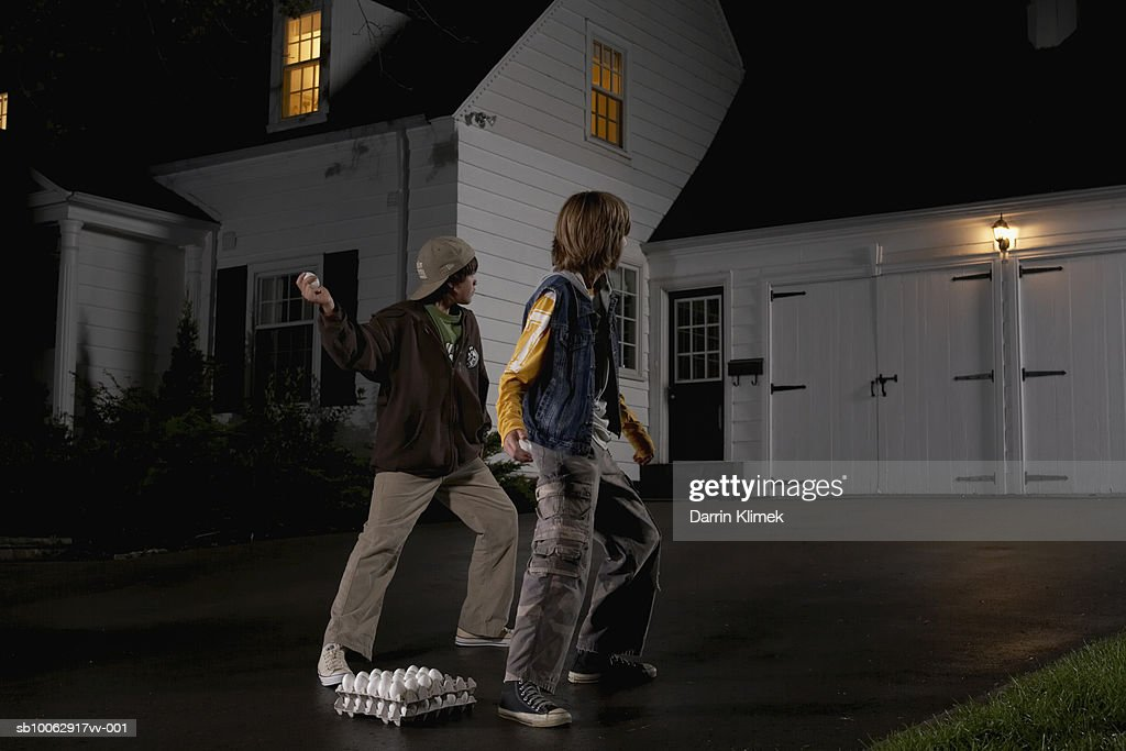 Two boys (12-13) standing in driveway, throwing eggs at house, night, rear view : Stock Photo