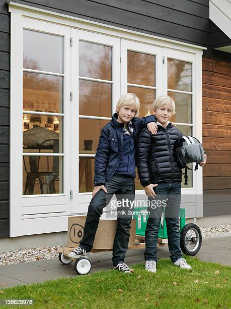 Two boys standing in front of house