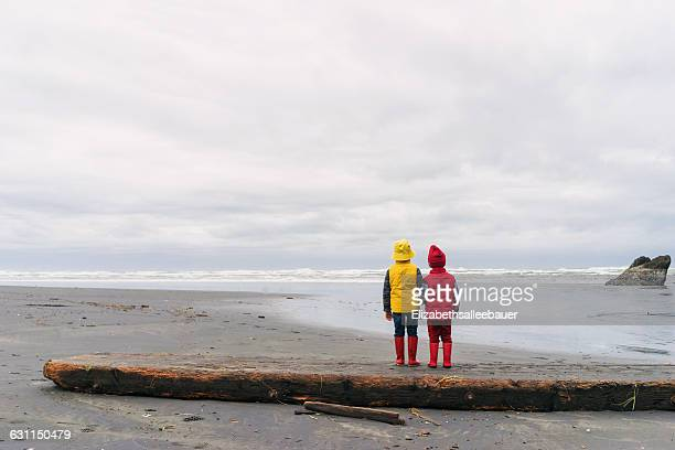 Two boys standing on beach arm in arm