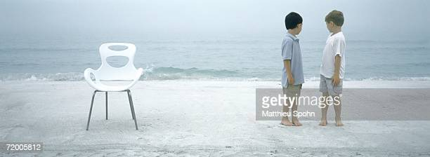 Two boys standing on beach, looking over shoulders at ocean