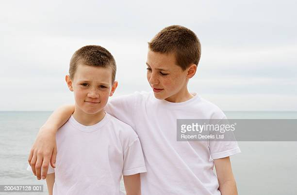 two boys (11-13) standing on beach, one with arm around the other - braço à volta imagens e fotografias de stock