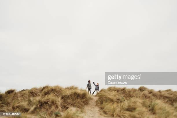 two boys standing on top of sand dune - 平地 ストックフォトと画像
