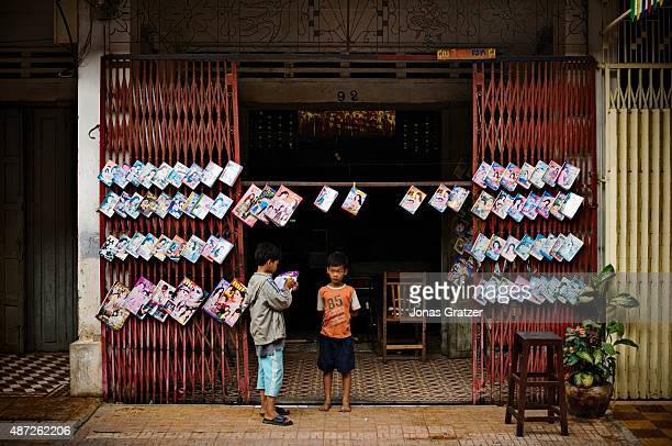 Two boys standing outside the local bookshop in Battambang