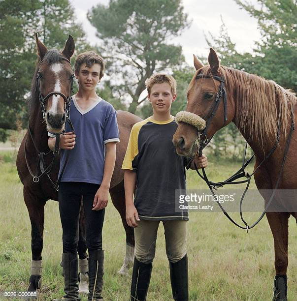 Two Boys Standing with Horses