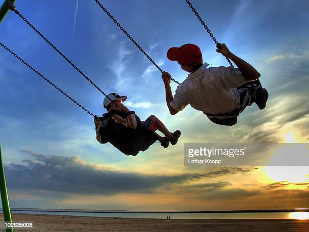 two boys swinging, enjoying the sunset - lower saxony stock pictures, royalty-free photos & images