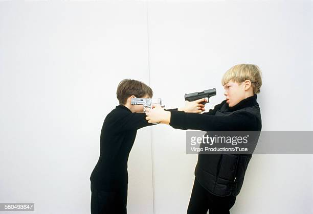 Two boys threatening themselves with guns