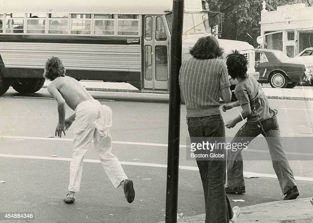 Two boys throw objects at a bus carrying black students through Edward Everett Square in Dorchester on Sept 12 the first day of school under the new...