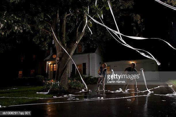 Two boys (12-13) throwing toilet paper into tree in front of house, night