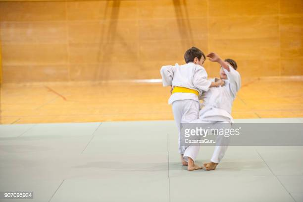 two boys training judo - martial arts stock pictures, royalty-free photos & images
