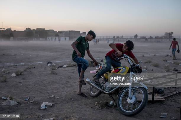 Two boys try to start a motorbike at a football field in East Mosul on November 5 2017 in Mosul Iraq Five months after Mosul Iraq's secondlargest...