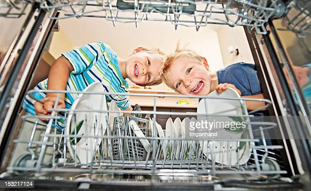 Two boys unloading a dishwasher