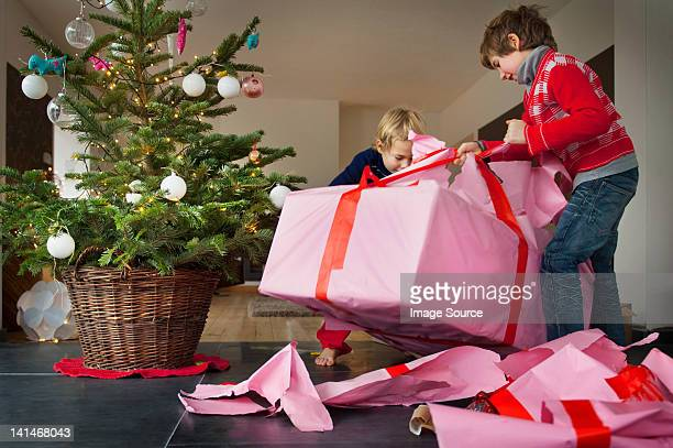 Two boys unwrapping Christmas presents