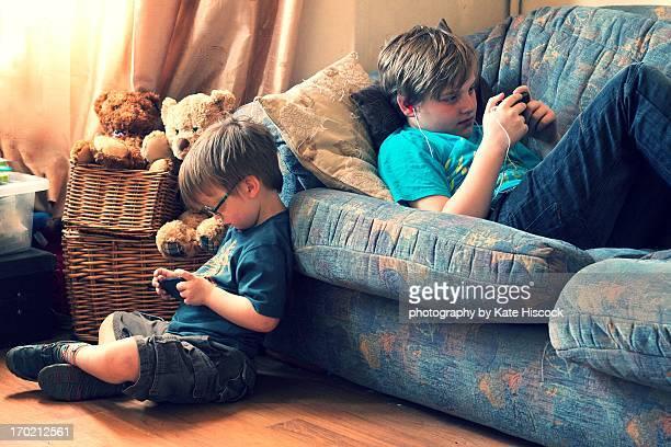two boys using smartphones