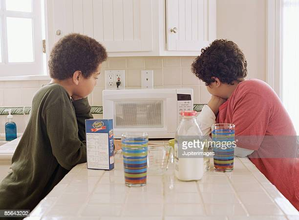 Two boys waiting for microwave oven to finish cooking