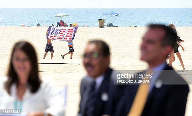 Two boys walk across the beach holding a USA flag as Los Angeles Mayor Eric Garcetti and former US Olympic Swimmer Janet Evans listen as sportscaster...