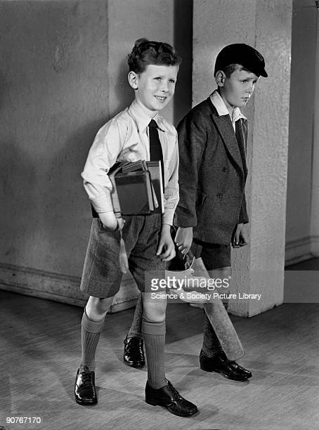 Two boys walk along a corridor one carrying a cricket bat and the other books Photographs of bright smiling boys and girls were used by advertisers...