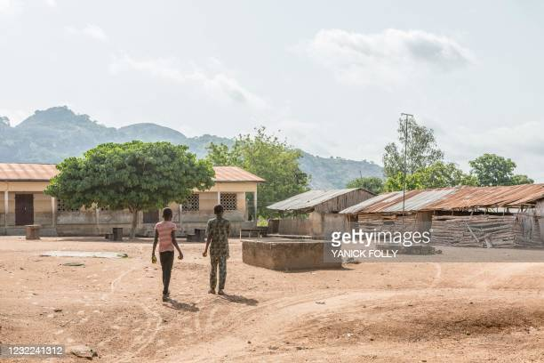 Two boys walk at a polling station at the public primary school of Kpabai in Save, Benin, on April 11, 2021. - On April 8 in the central city of...