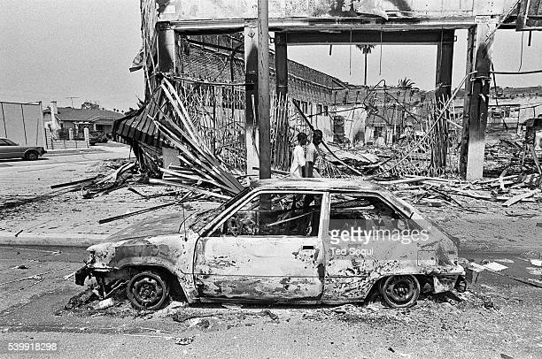 Two boys walk by riot damage on Adams Blvd in South Central Los Angeles Los Angeles has undergone several days of rioting due to the acquittal of the...