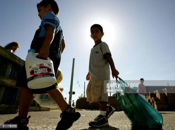 Two boys walk with their mother after picking up free food and household items at a distribution station sponsered by Convoy Of Hope August 16 2004...