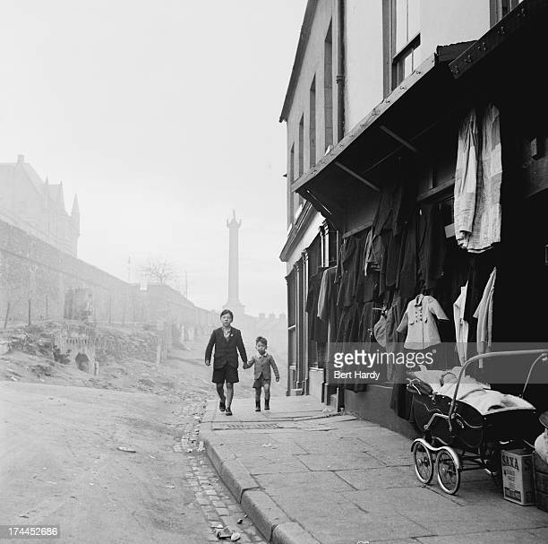 Two boys walking down a street in Derry Northern Ireland 25th November 1955 On the left are the city walls and behind them is the Walker Memorial...