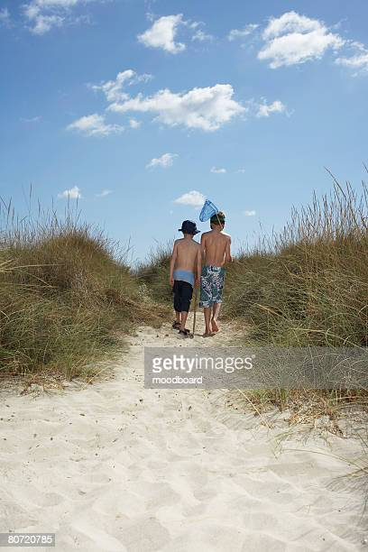 Two boys (6-11) walking in sand dunes with fishing net back view