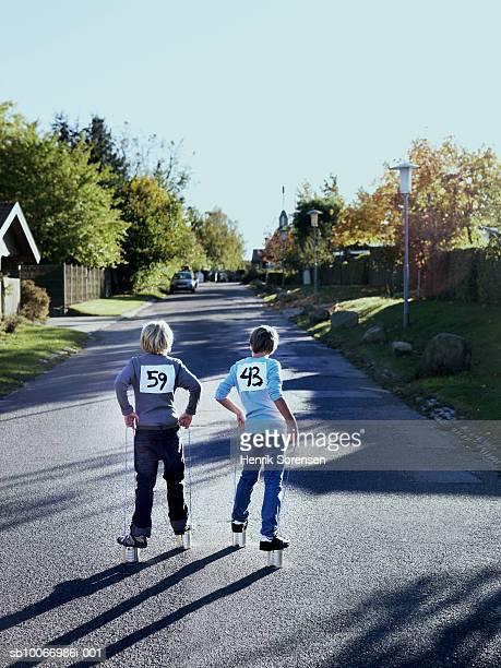 Two boys (8-11) walking on can stilts