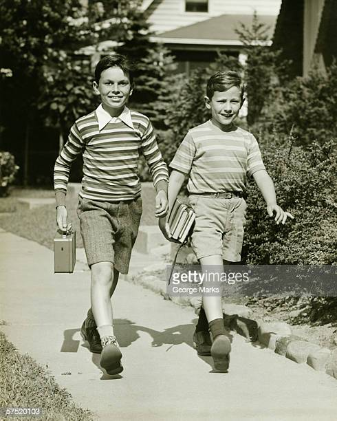 Two boys (10-11) walking side by side in suburbs, carrying books, (B&W)