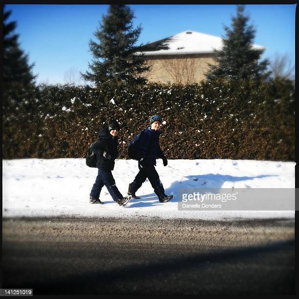 Two boys walking to school in winter